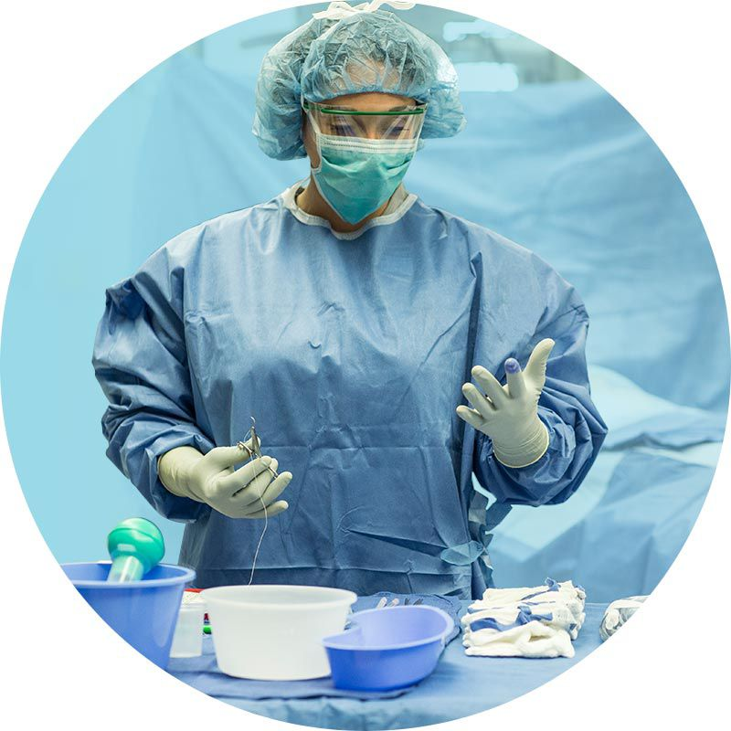 surgeon in full protection standing in front of a table of surgical supplies