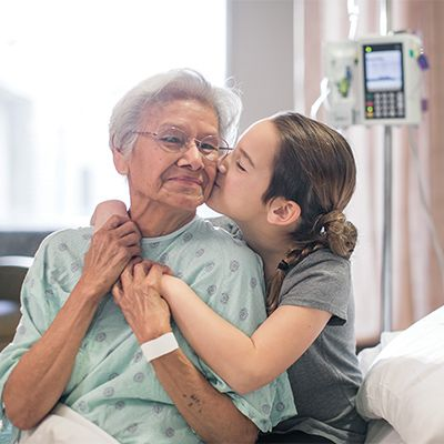 Young granddaughter kissing grandmother who is a patient wearing a hospital gown.
