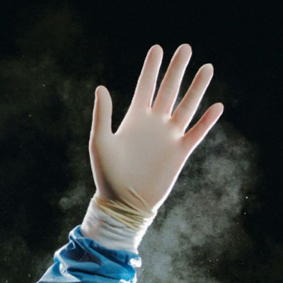 Hand in front of black background wearing powdered glove with powder in the air.