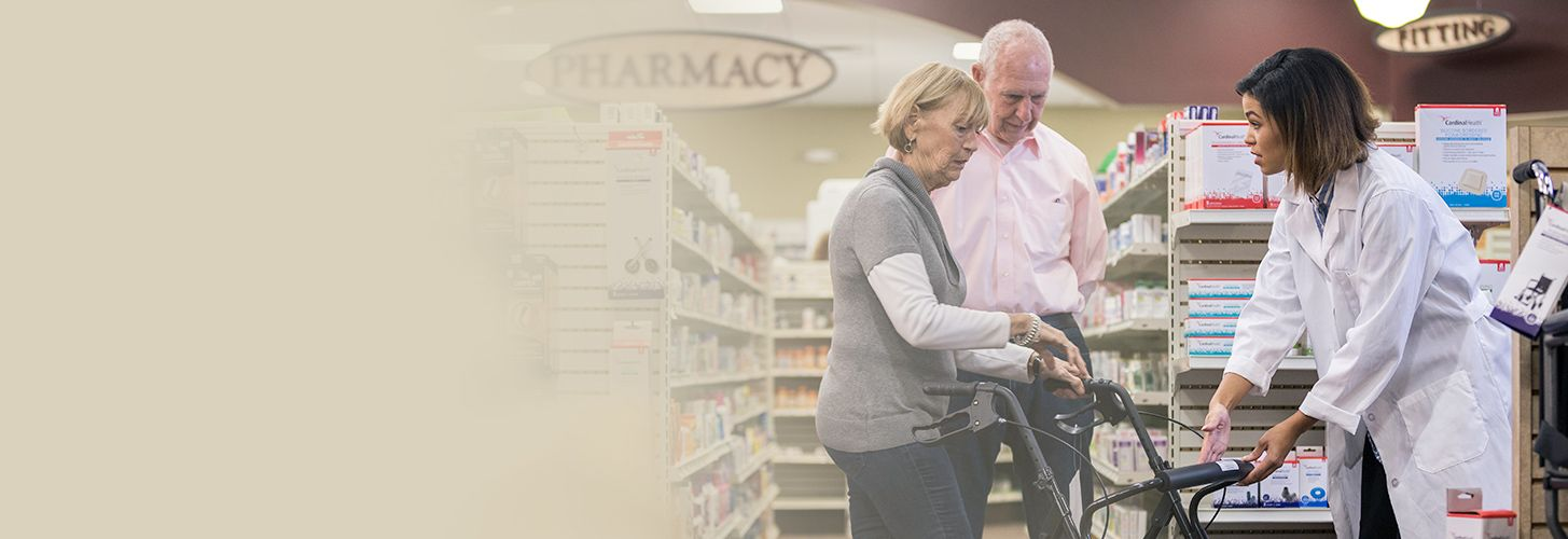 Pharmacist showing elderly customers how to use rollator.