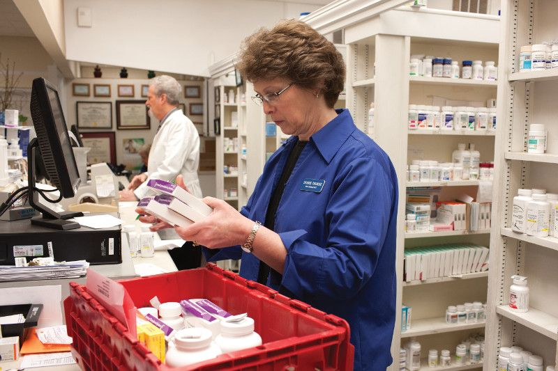 Pharmacist reviewing inventory from a Cardinal Health delivery tote at a retail independent pharmacy.
