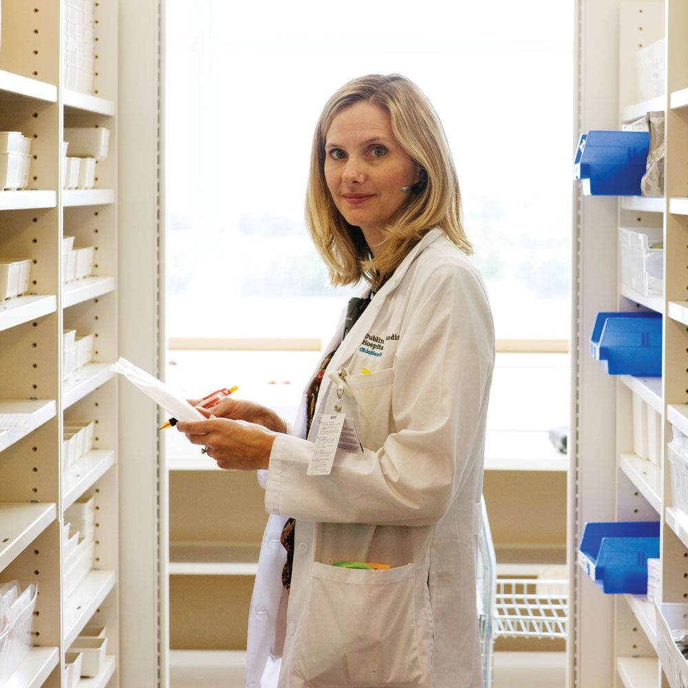 pharmacist with paper and pen in front of supply shelves
