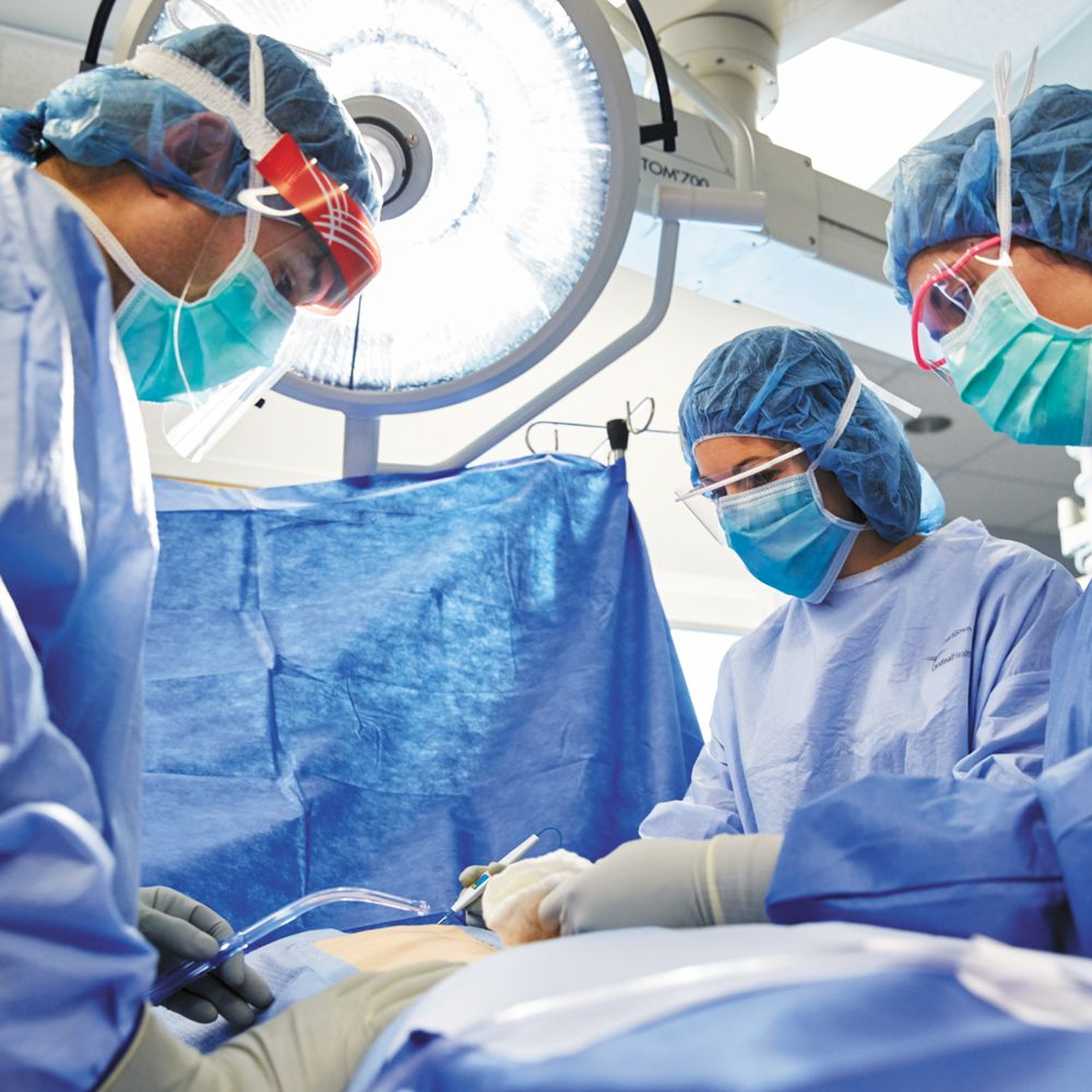 surgeons in full protective gear in operating room performing surgery
