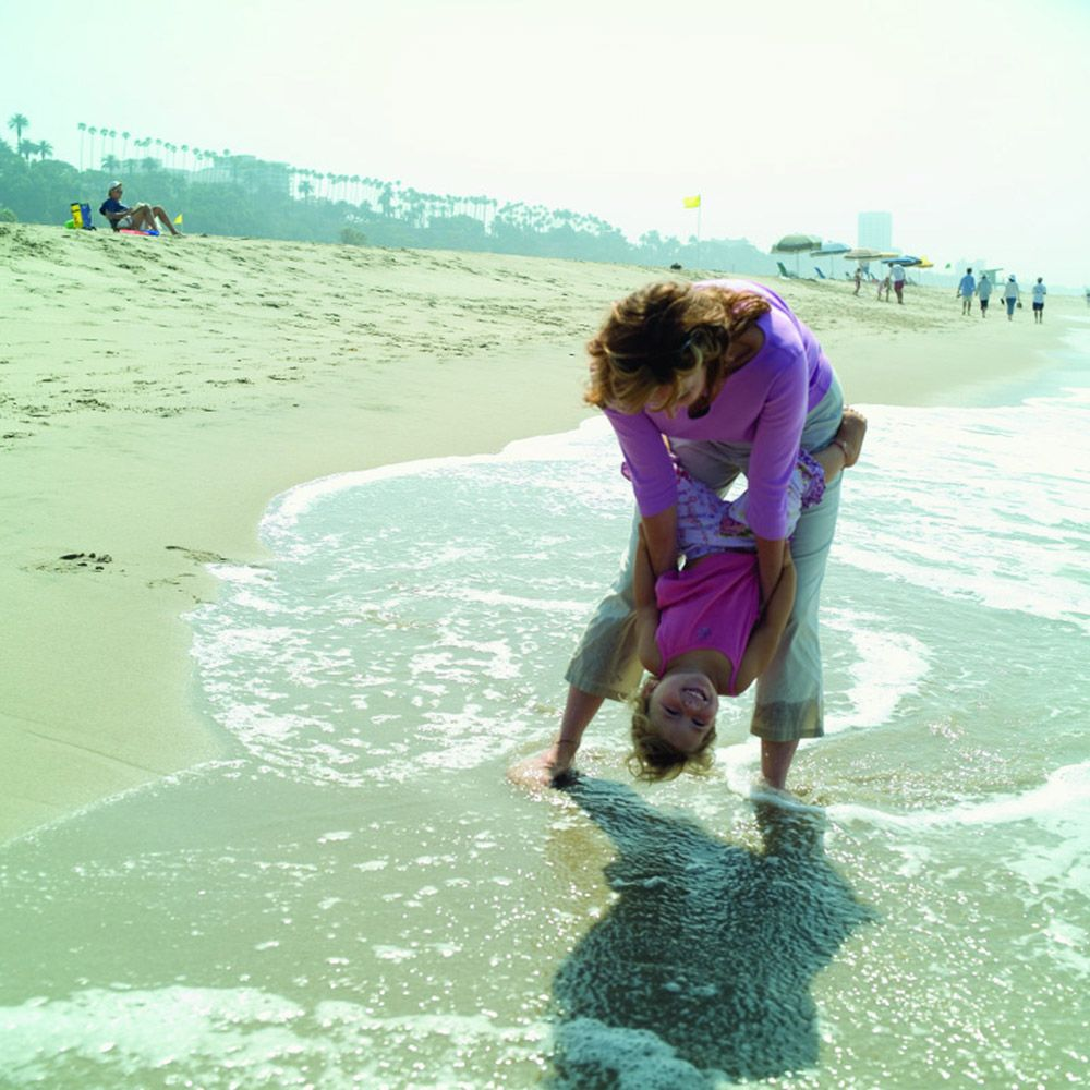 mother playing with young daughter on beach at edge of water