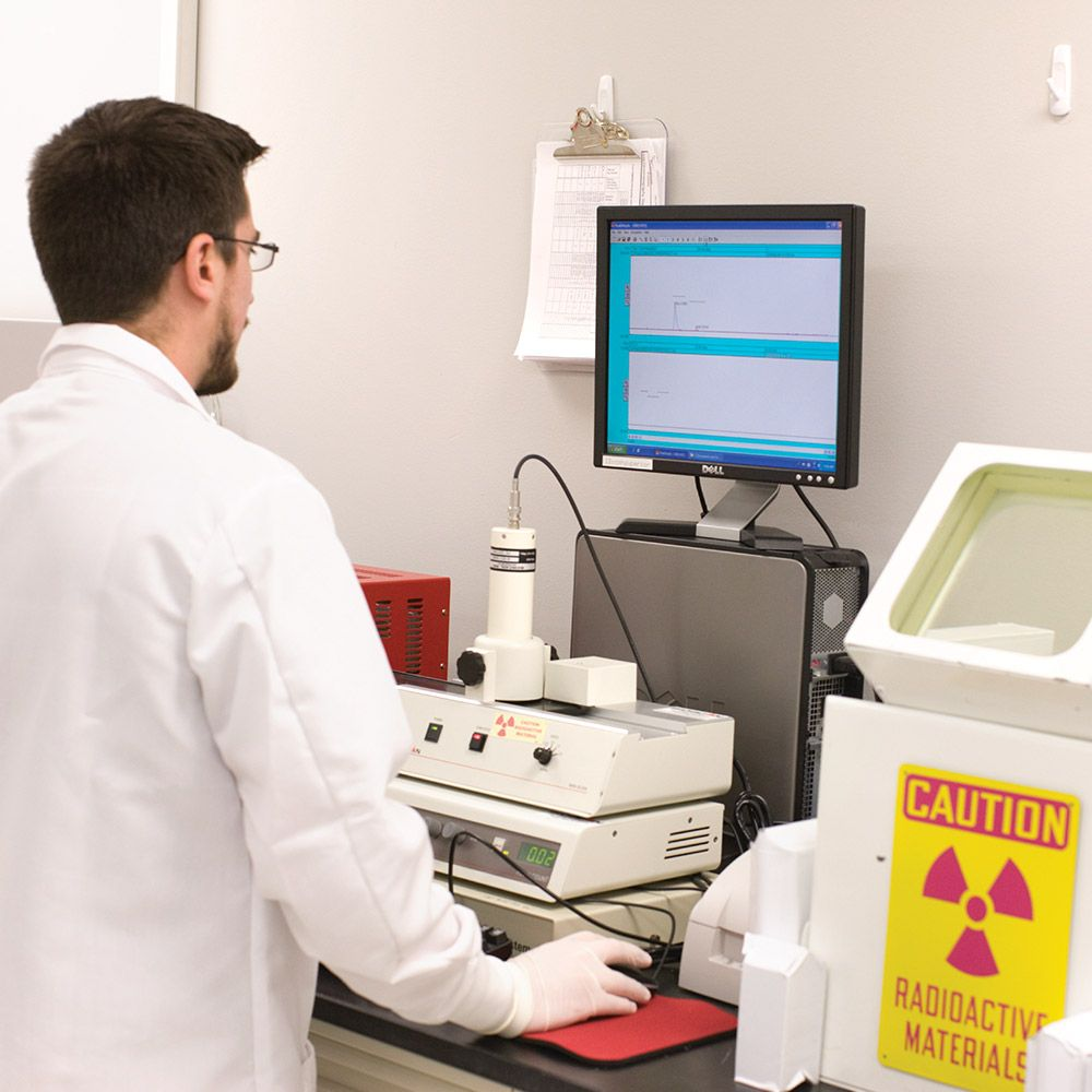 Nuclear pharmacist looking at a computer monitor.