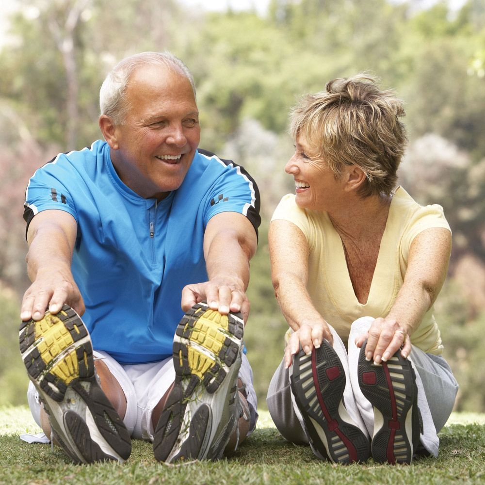 Active couple sitting on ground to stretch