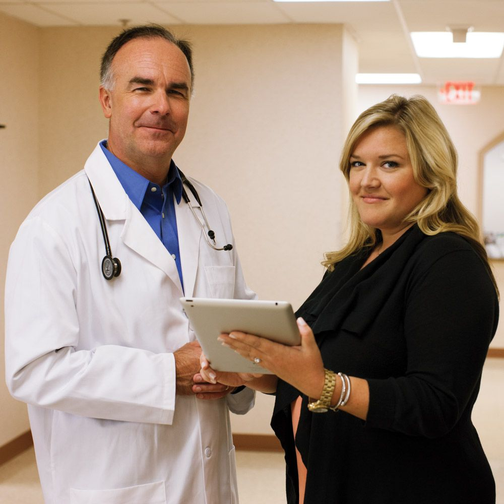 Sales rep showing a doctor something on a tablet.