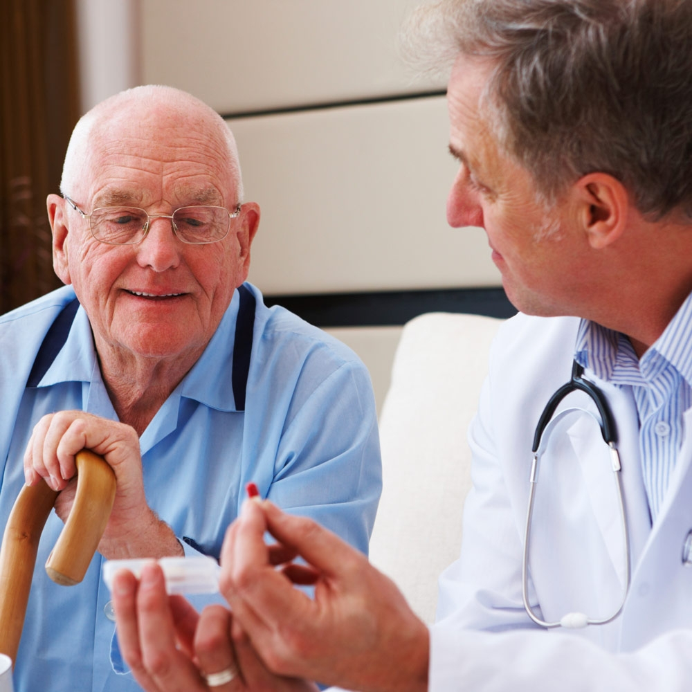 doctor meeting with elderly patient with cane