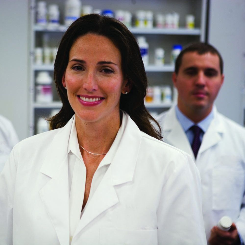 male and female pharmacists in front of shelves