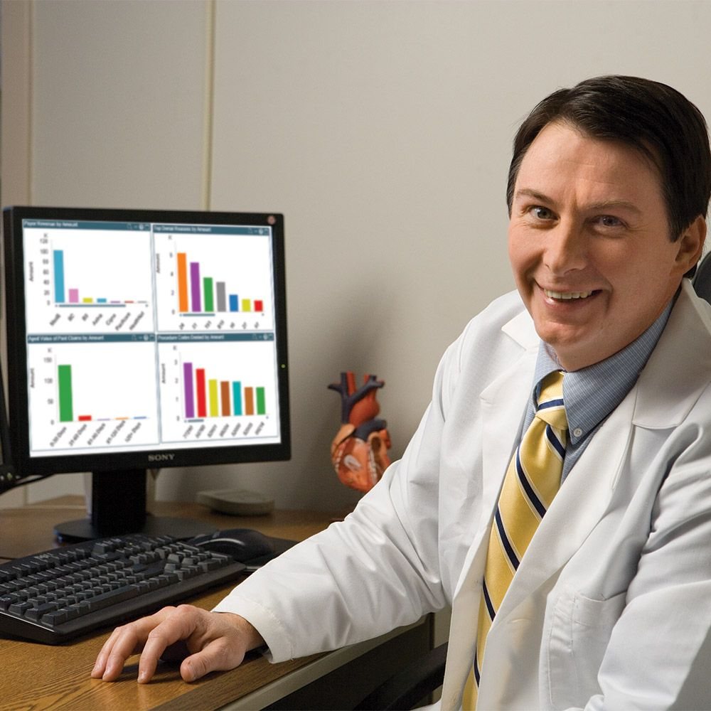 pharmacist in front of computer with graphs on screen