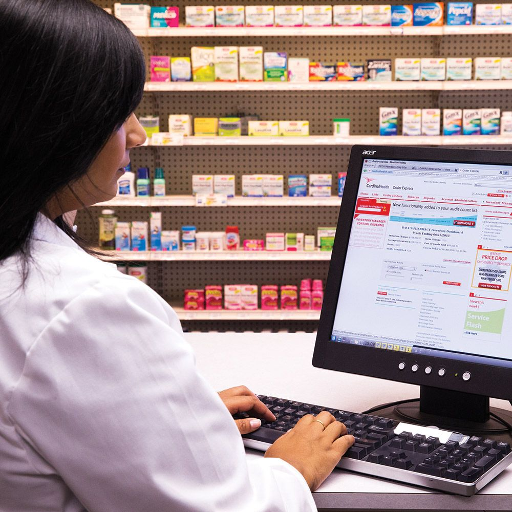 pharmacist using Order Express application on computer, in front of shelves