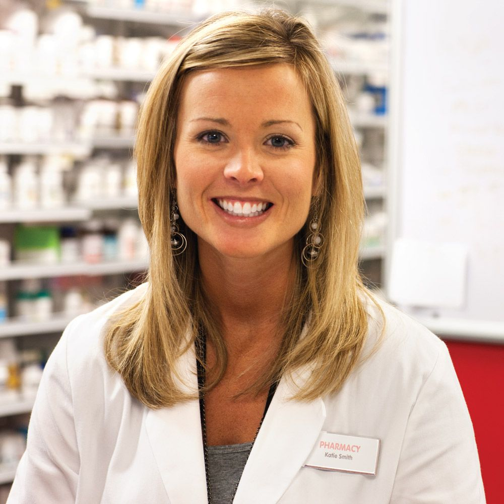 pharmacist in front of shelves, smiling