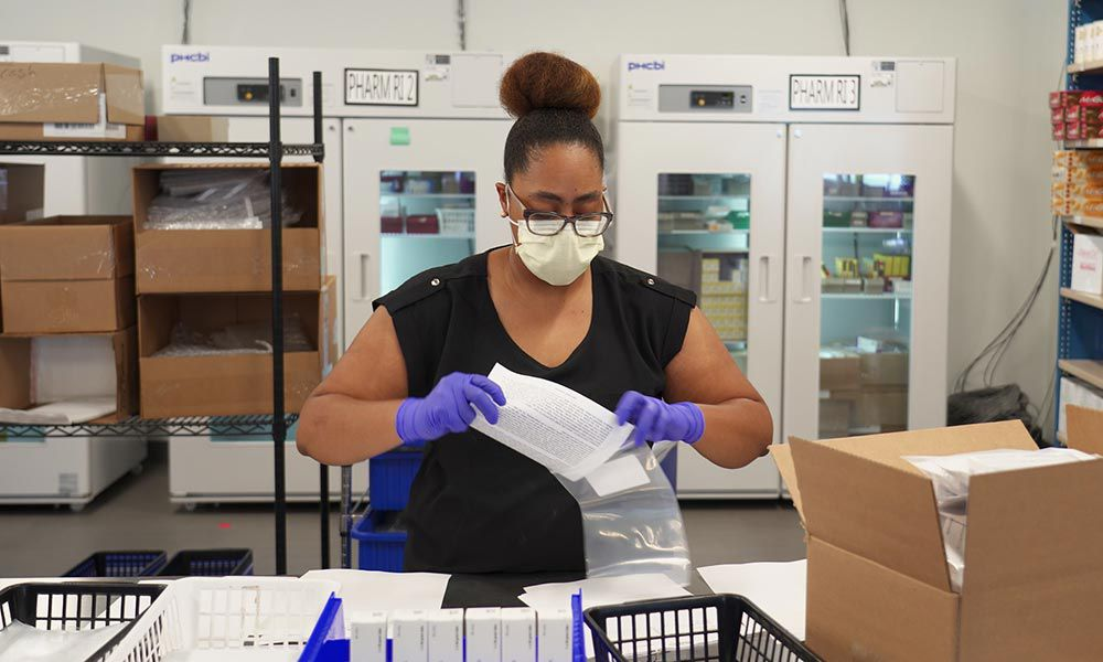 Employee wearing a face mask putting a packing slip into a bag.