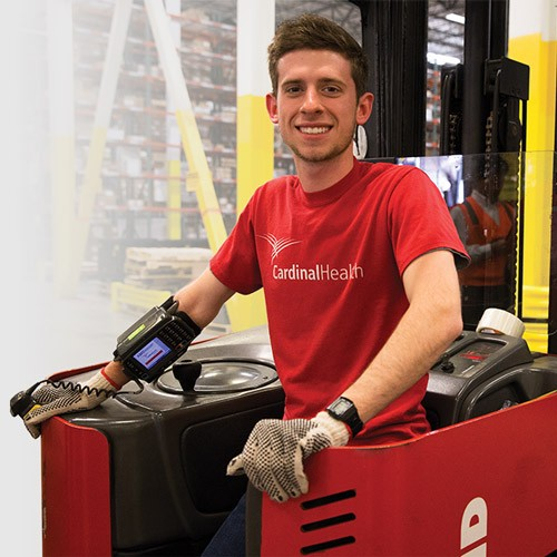 Associate standing on forklift and smiling.