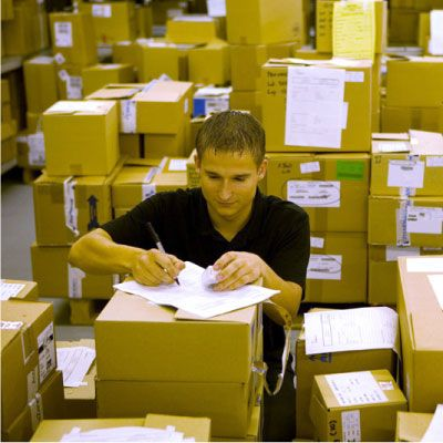 associate in distribution center surrounded by many boxes, writing on paper
