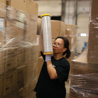associate at distribution center wrapping pallet of boxes with cellophane