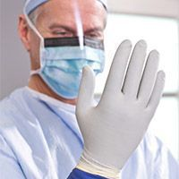 surgeon looking at his hand wearing a surgical glove