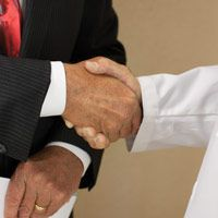 hand of man wearing suit shaking the hand of a man wearing a white lab coat