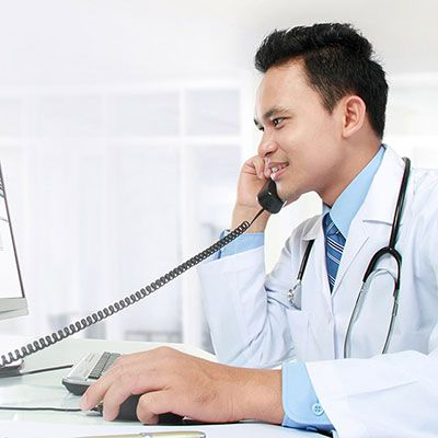 physician on phone looking at computer monitor.