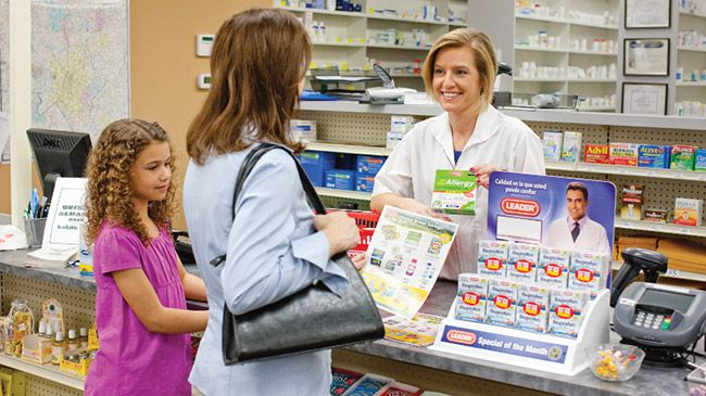Pharmacist handing prescription to patient with daughter