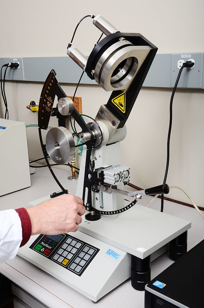 Technician using Instron® tensile tester.