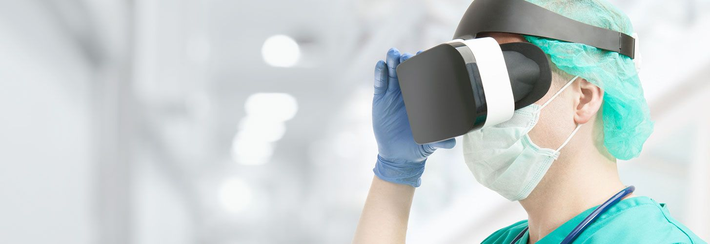 Doctor wearing cap, mask, gloves, scrubs and stethoscope looking through VR headset.