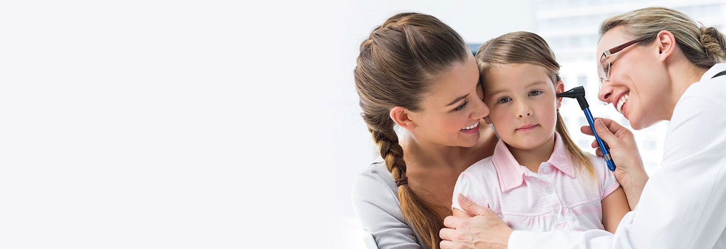 Smiling physician examining child's ear while mother hugs child.