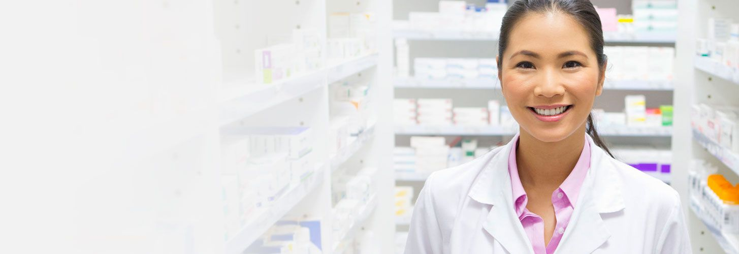 Smiling pharmacist standing in pharmacy.