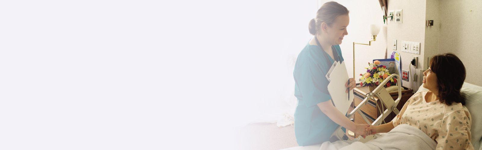 doctor visiting patient at bedside, holding hands