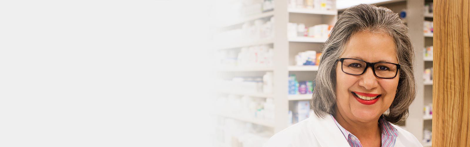 Smiling pharmacist wearing glasses and standing in front of the pharmacy shelves.