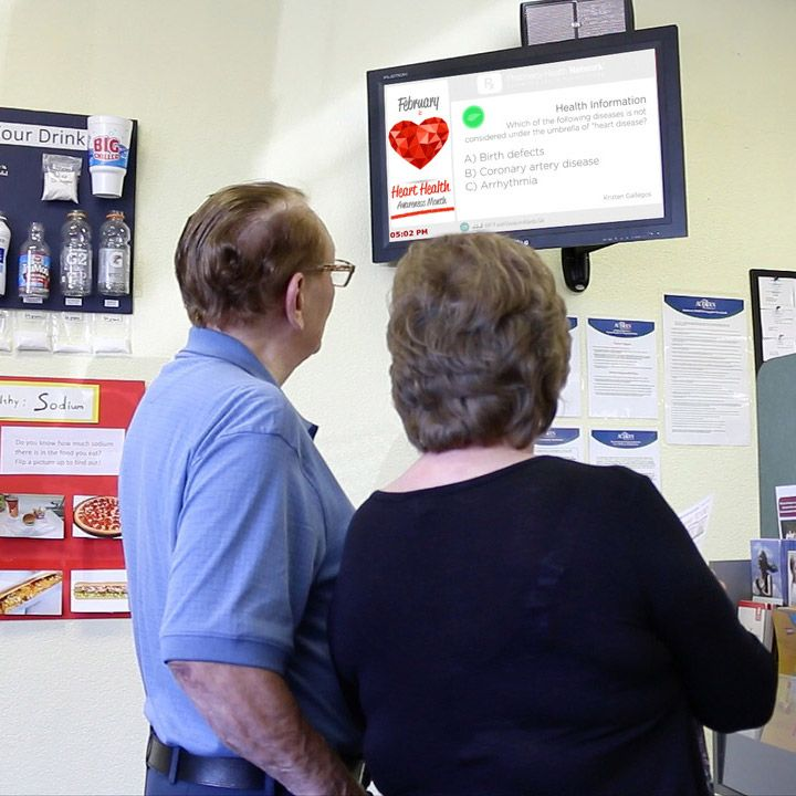 Elderly couple viewing Pharmacy Health Network material