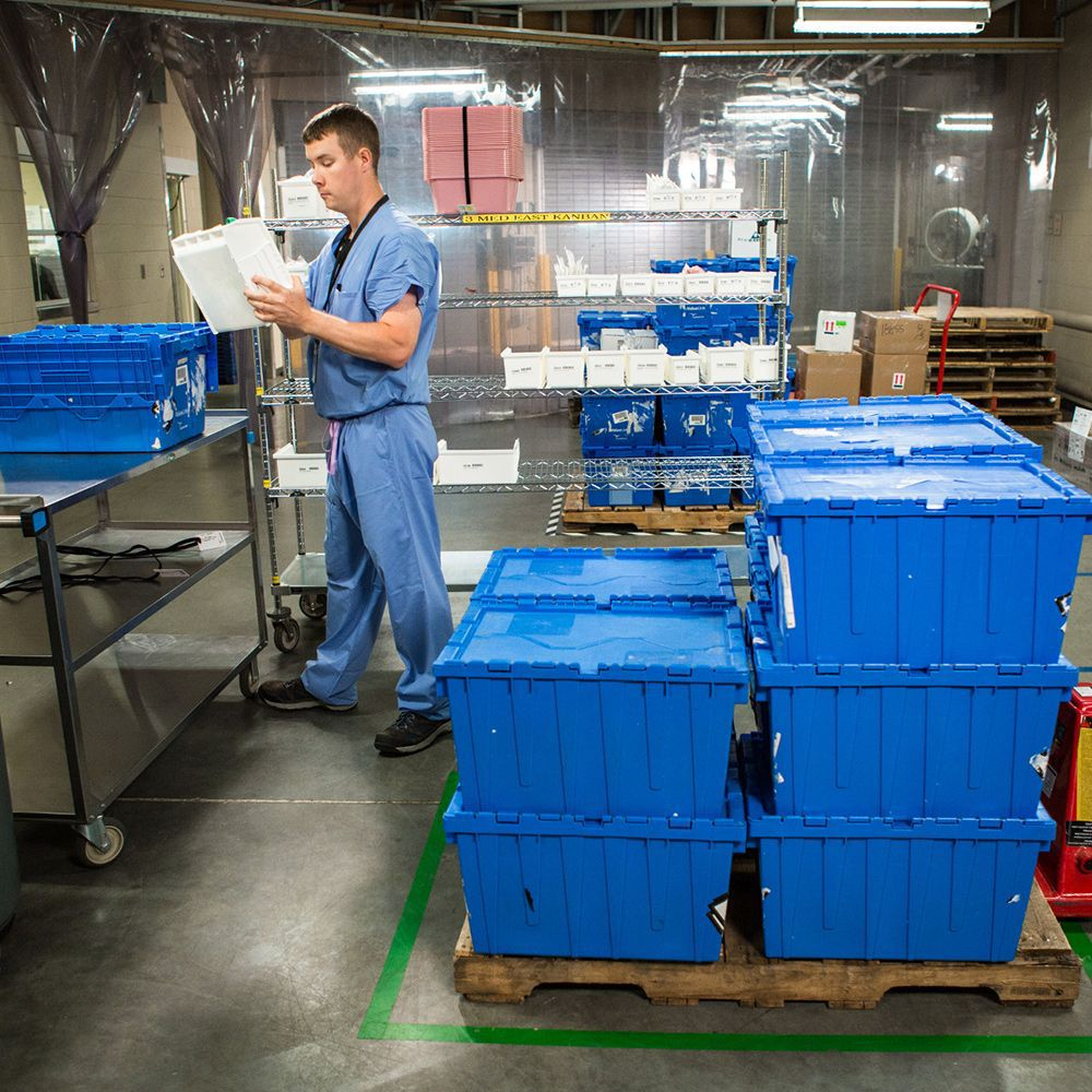 Man in scrubs sorting blue totes.