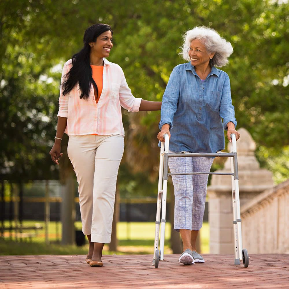Elderly patient walking in park using Cardinal Health's folding walker with wheels, while being assisted by an aid.
