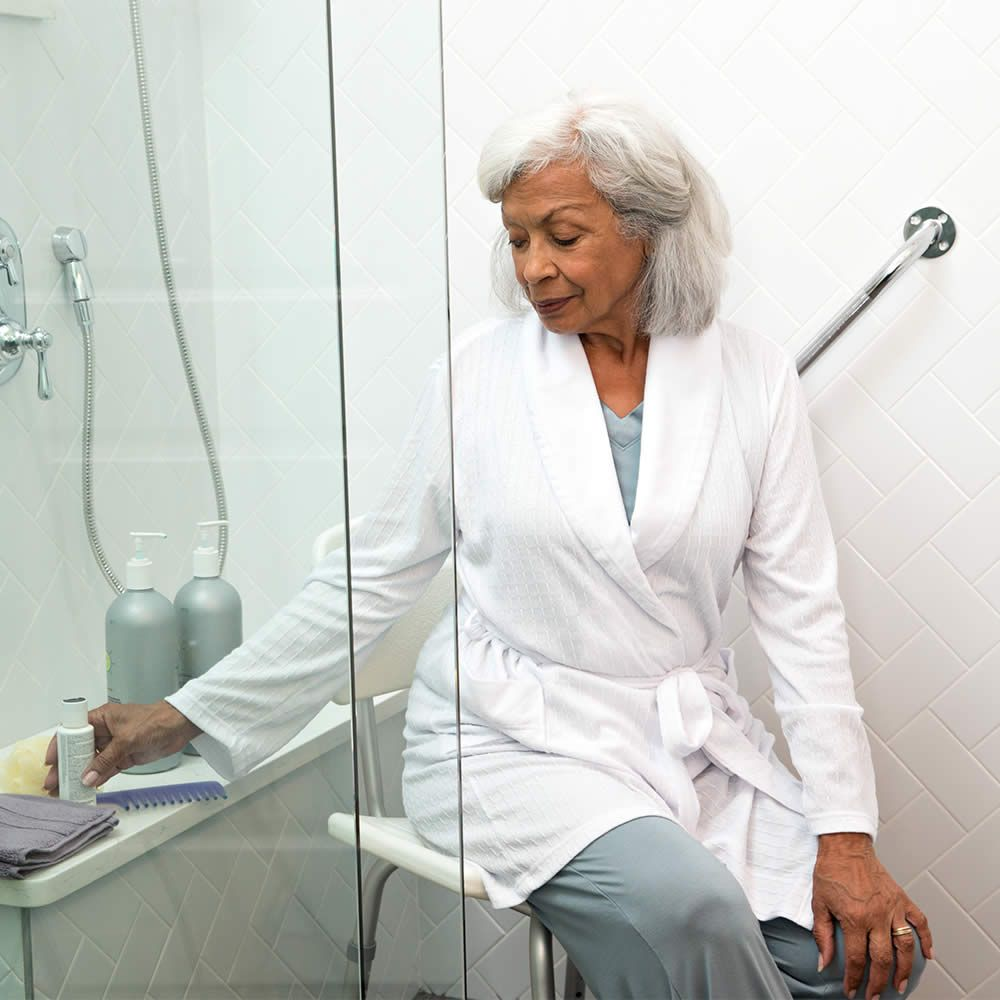 Elderly patient in robe sitting on shower chair.
