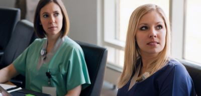 Two nurses wearing scrubs in a meeting.