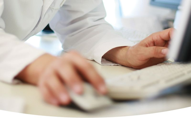 medical professional in white coat using computer and mouse