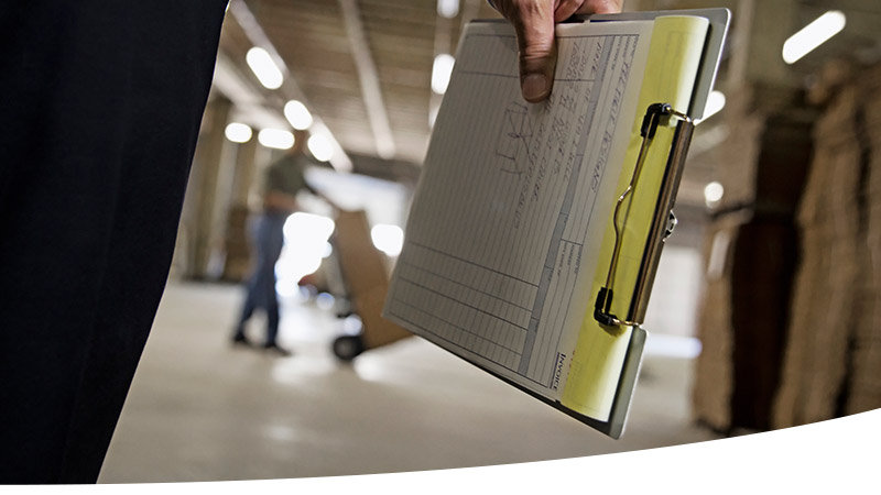 associate carrying clip board with another associate in the background pushing a hard cart full of boxes