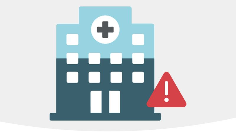 Graphic of hospital with red warning symbol.