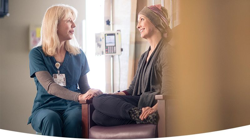 Nurse talking with a patient receiving chemotherapy.