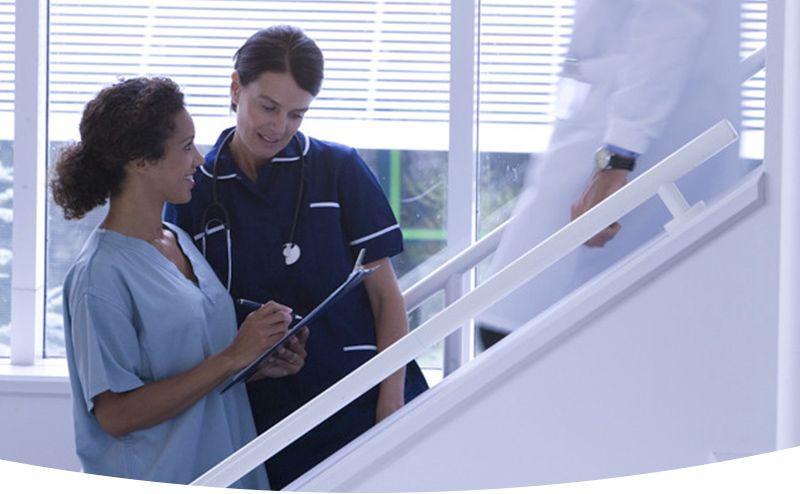 Physician and nurse on stairs looking at clipboard and talking.