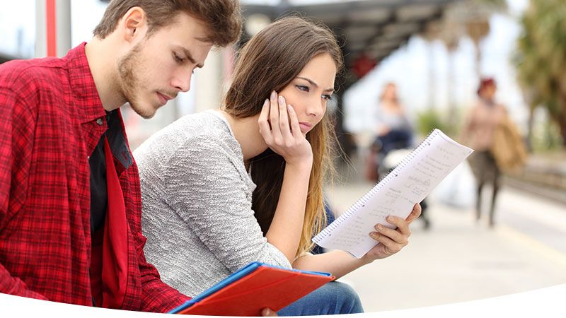 Male and female students sitting on bench looking at class notes.