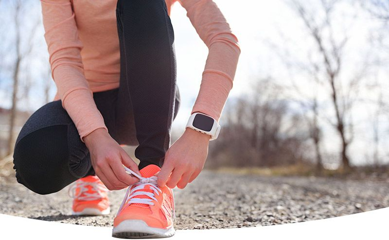 Runner tying shoes, wearing digital tracking device on wrist.