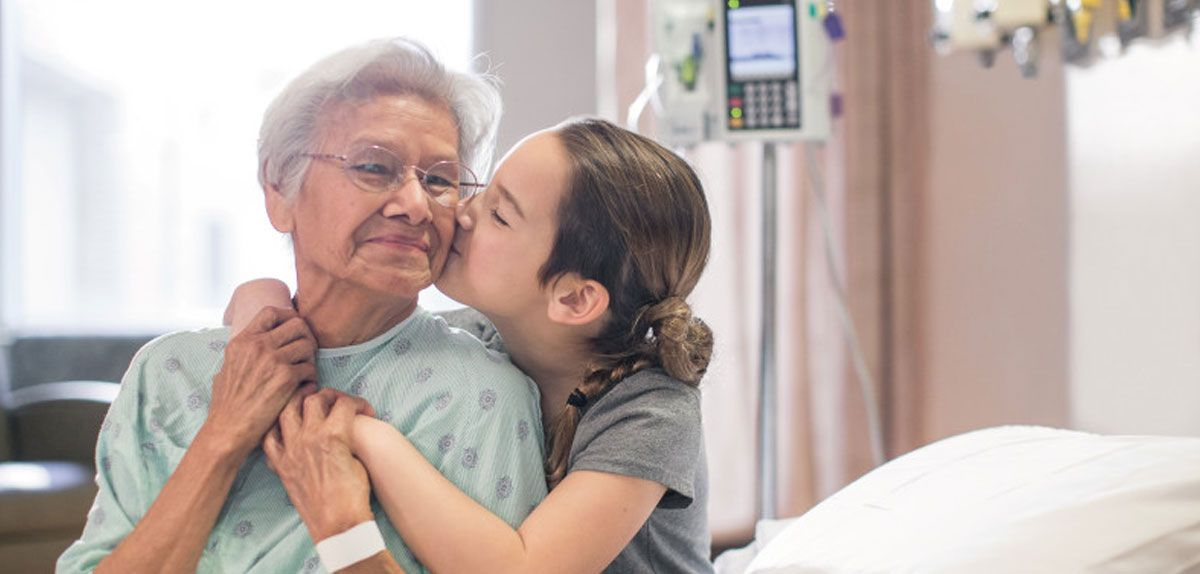 Patient in hospital gown receiving a hug.
