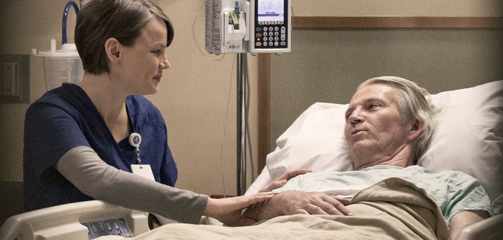 Nurse comforting a patient in a hospital bed.
