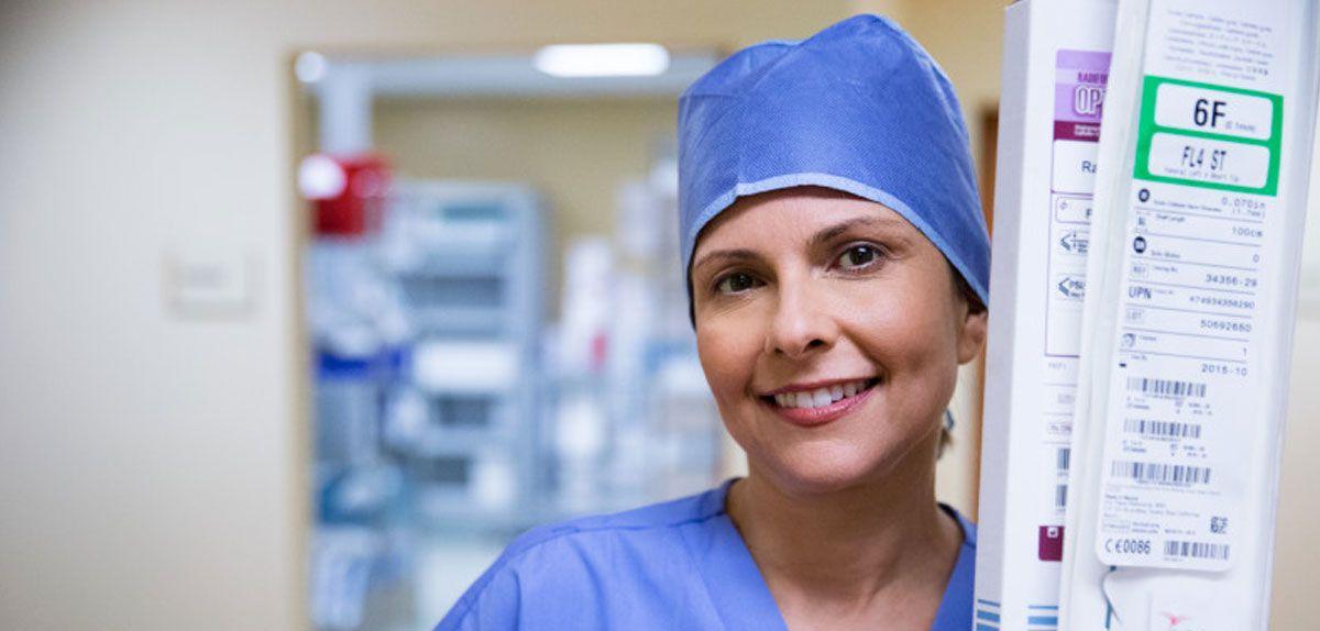 Nurse holding medical supplies.