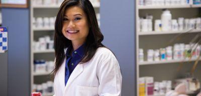 female pharmacist in front of stocked shelves.