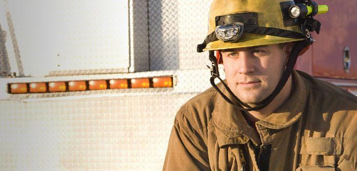 fireman wearing helmet and jacket beside fire truck