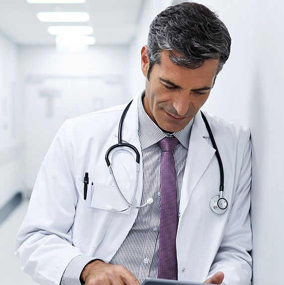 physician with stethoscope reviewing information