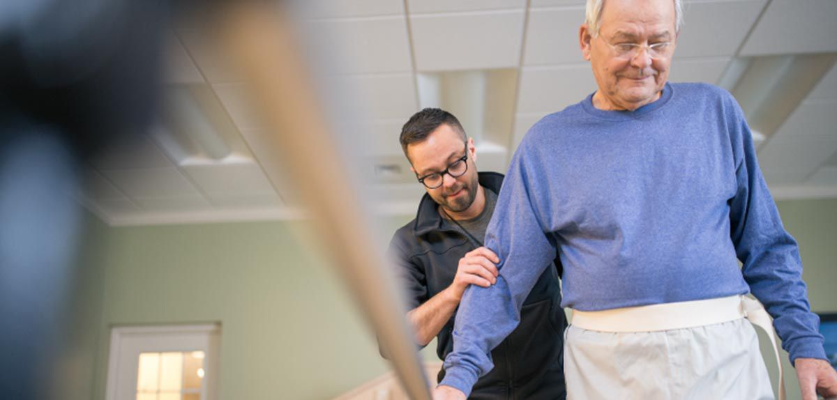 Physical therapist helping a patient walk.