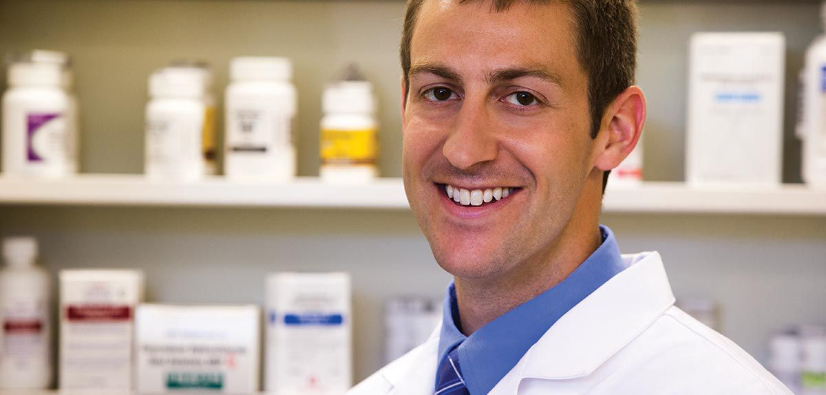 Smiling pharmacist with medication bottles in background.